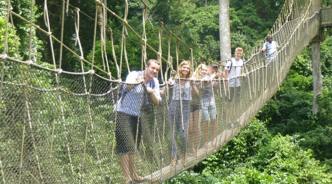 While doing community volunteer work in Ghana, teenagers use the weekends to visit local attractions like a forest walk.